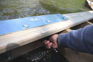 To mount the platform to the gangway, we used two heavy-duty brackets called Chain Pile Holders, which we bolted to the rim joist and the last row of decking.
