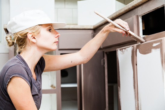 Closeup of Woman Holding Paint Brush and Painting Kitchen Cabinets