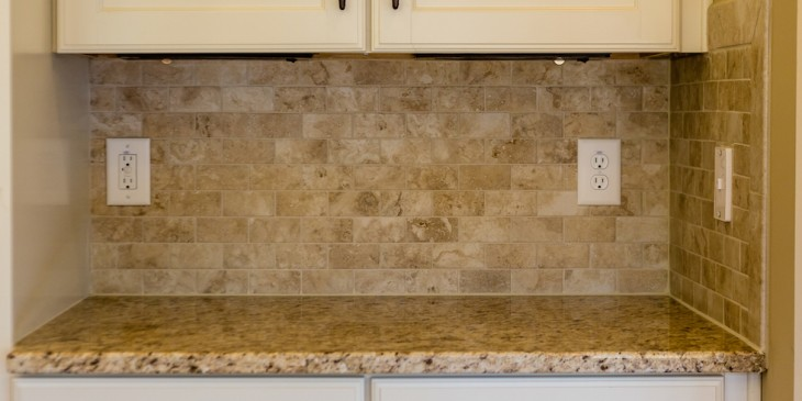 Granite countertops and tile backsplash on white cabinets in new modern kitchen