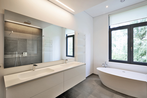 Bathtub in corian Faucet and shower in tiled bathroom with windows towards garden