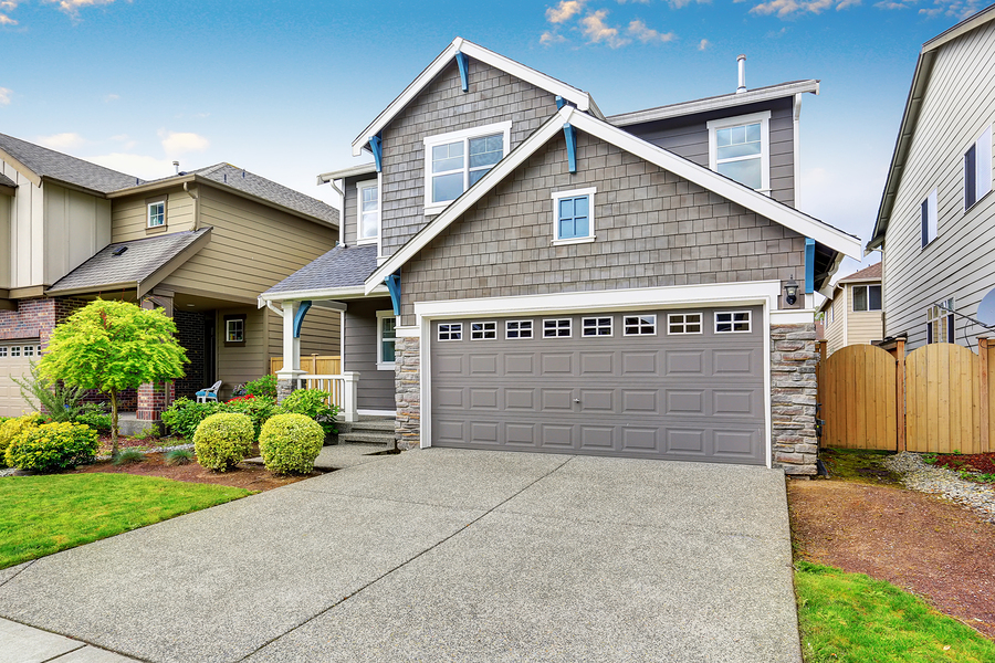 Nice curb appeal of two level house mocha exterior paint and concrete driveway. View of cozy small porch